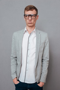 Young man in suit and glasses. hands in pockets. looking away. isolated gray background