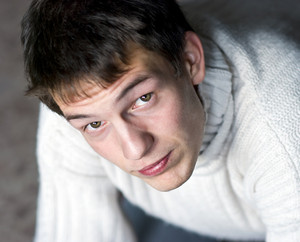 Young man in sweater is looking up.