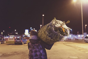 Young man in town carrying a christmas tree