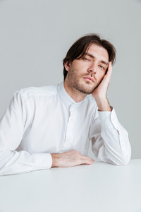 Young man in white shirt sleeping while sittng at the desk isolated on the gray background