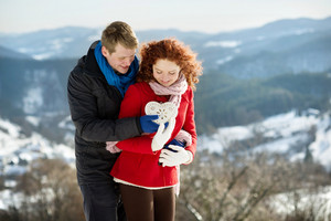 Young man is giving heart to a beautiful girl in snowy land