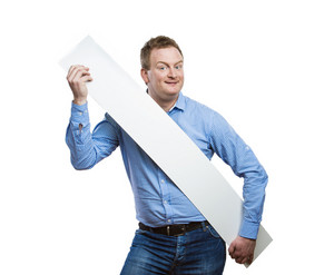 Young man making funny face, holding a blank sign board. Studio shot on white background.