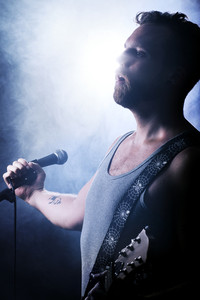 Young man playing rock concert. Play guitar.