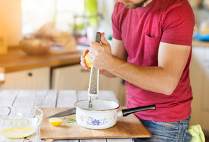 Young man preparing a sauce in his domestic kitchen