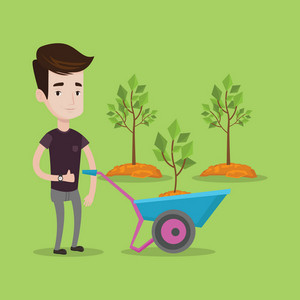 Young man pushing wheelbarrow with plant and dirt in the park. A gardener with wheelbarrow on a background of newly planted trees. Vector flat design illustration. Square layout.