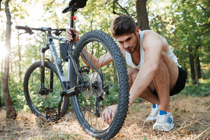Young man repairing mountain bike in the forest. problems with wheel