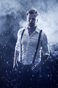 Young man / rocker with ear rings walking in the snow with smoke in the background .