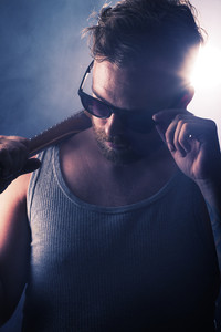 Young man / rocker with guitar and sunglasses. Smoke and scene light.