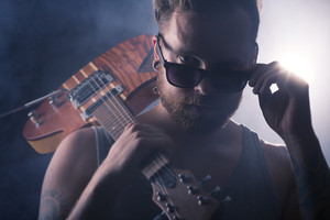 Young man / rocker with guitar and sunglasses.
