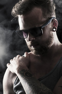 Young man / rocker with sunglasses, tattoos and ear rings. Smoke and scene light.
