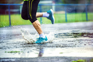 Young man running on asphalt sports field in rainy weather. Details of legs and sports shoes splashing in puddles.