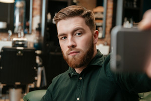 Young man sitting in armchair at barbershop and take a selfie. Focus on man.
