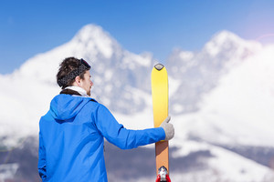 Young man skiing outside in sunny winter mountains