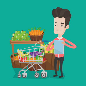 Young man standing near trolley full with products. Customer holding shopping list on the background of supermarket section with vegetables and fruits. Vector flat design illustration. Square layout.