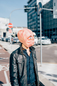 Young man wearing alien mask posing outdoor in the city- strange, halloween, carnival concept