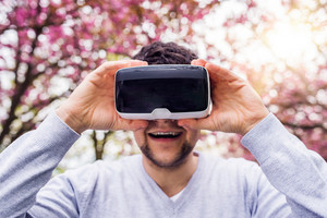Young man wearing virtual reality goggles outside in spring nature