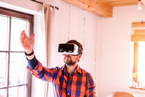 Young man wearing virtual reality goggles standing in a kitchen