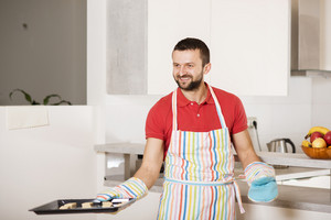 Young man with apron is cooking in the kitchen