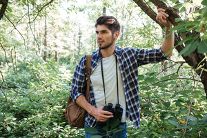 Young man with backpack near the tree looking away. man in shirt with binoculars