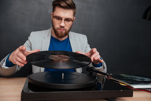 Young man with gramophone in studio. sitting on the table. isolated black background