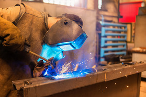 Young man with protective mask welding in a factory