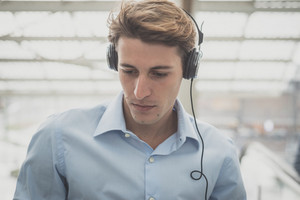 young model hansome blonde man with headphones in the city