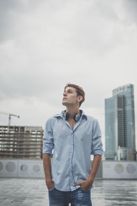 young model hansome blonde man with music headphones in the city