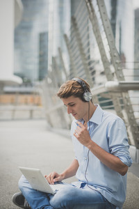 young model hansome blonde man with notebook and headphones in the city