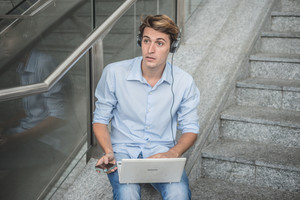 young model hansome blonde man with notebook smartphone and headphones in the city