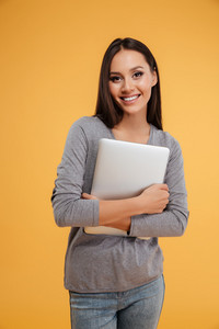 Young model holding laptop in hands. vertical image. isolated orange background