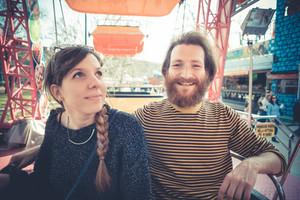 young modern stylish couple urban city carousel having fun playground