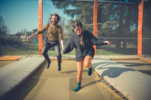 young modern stylish couple urban city jumping trampoline outdoors