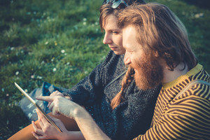young modern stylish couple using tablet in urban city outdoors