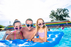 Young mother and father with their daughter in colorful sunglasses sitting on pool lilo in swimming pool in aqua park. Summer heat and water.