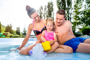 Young mother and father with their daughter in swimming pool in aqua park. Summer heat and water.
