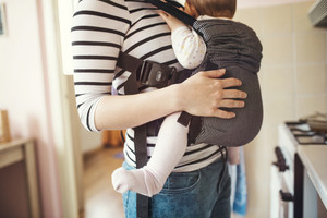 Young mother having her cute little daughter in baby carrier