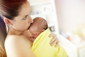 Young mother holding and kissing her newborn baby girl at home