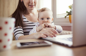 Young mother in home office with computer and her daughter