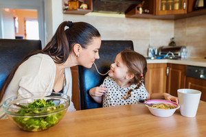 Young mother with her cute little daughter in the kitchen, eating spaghetti together
