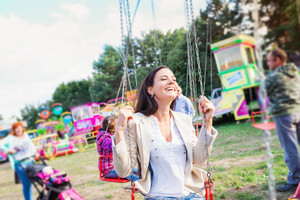 Young mother with her daughter having fun at fun fair, chain swing ride, amusement park