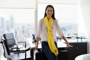 Young multiethnic Chinese Hispanic female entrepreneur leaning on table in a modern office building, with sight of the city. She looks at camera and smiles happy