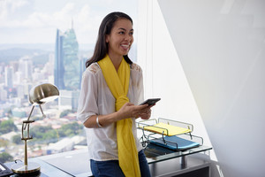 Young multiethnic Chinese Hispanic woman leaning on table in a modern office building, with sight of the city. She holds a mobile phone and smiles happy