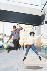 Young multiethnic couple jumping outdoor in the city - satisfaction, achievement, happiness concept