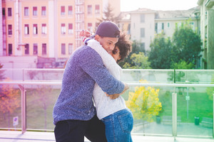 Young multiethnic couple outdoor in the city having fun hugging - love, happiness, friendship concept
