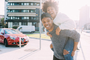 Young multiethnic couple outdoor in the city having fun, she is riding piggyback - love, happiness, friendship concept