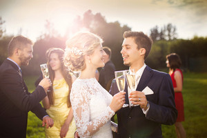 Young newlyweds and wedding guests clinking glasses at wedding reception outside