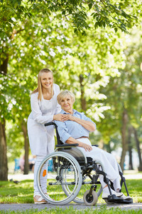 Young nurse and senior patient in a wheelchair looking at camera in park