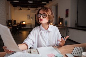 Young office woman. sits by the table