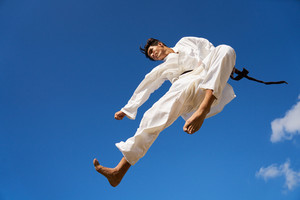 Young people, athlete, sport activity, combat and extreme sports. Hispanic man exercising in karate and traditional martial arts, jumping mid-air in the sky