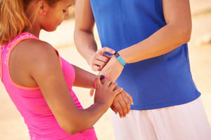Young people doing sport activities, friends running, using fitband watch, man and woman jogging on the street. Concept of leisure, health, recreation, fitness, exercise, training